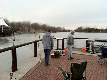 (From left) Chris West and Bill Markle were packed in tight to the corner in hopes of catching a carp swimming out of the stream that joins the Inner Harbor.