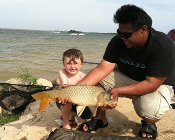 Club Director Josef Raguro helping an excited young angler handle a common carp